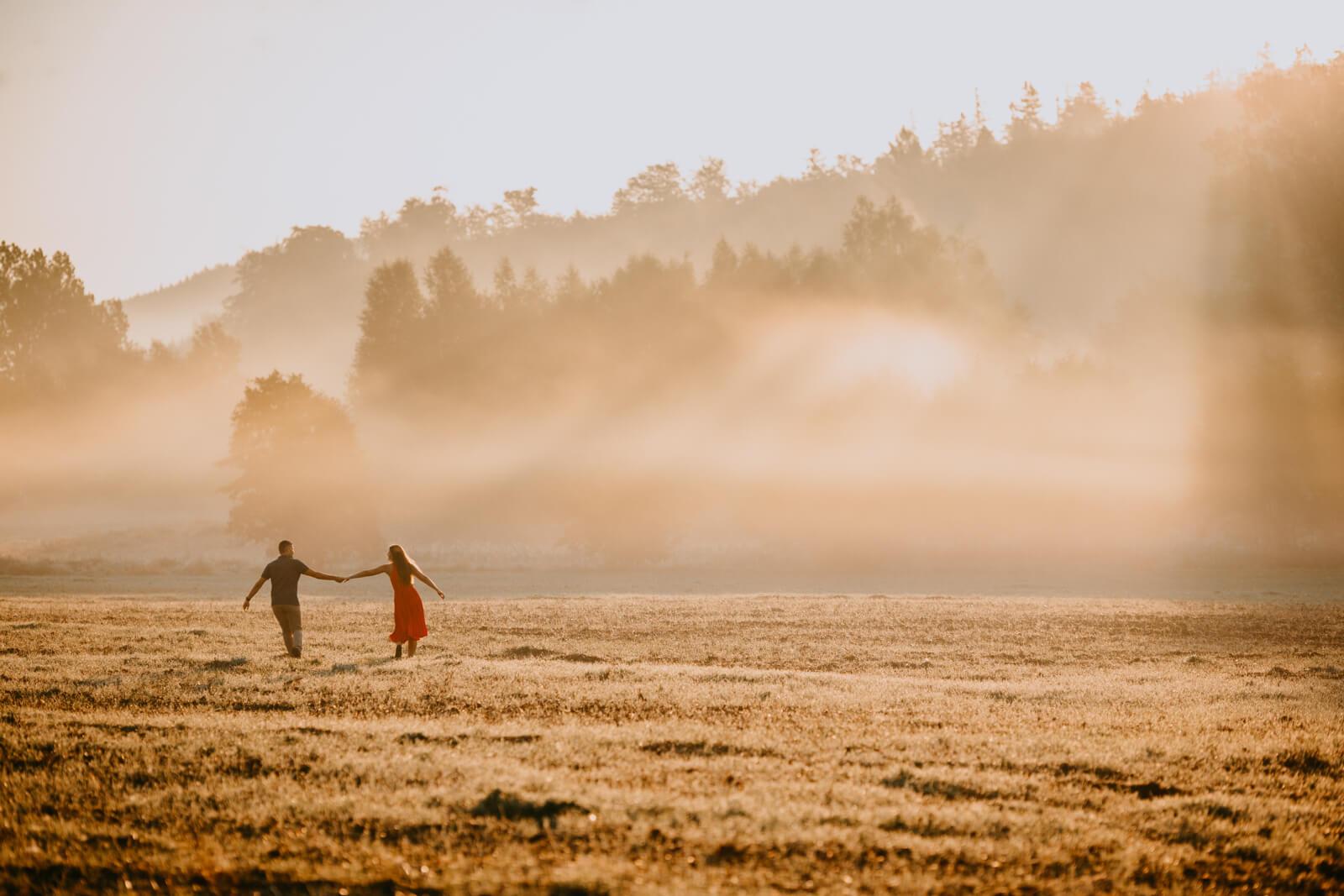 spacerująca po polu para o wschodzie słońca