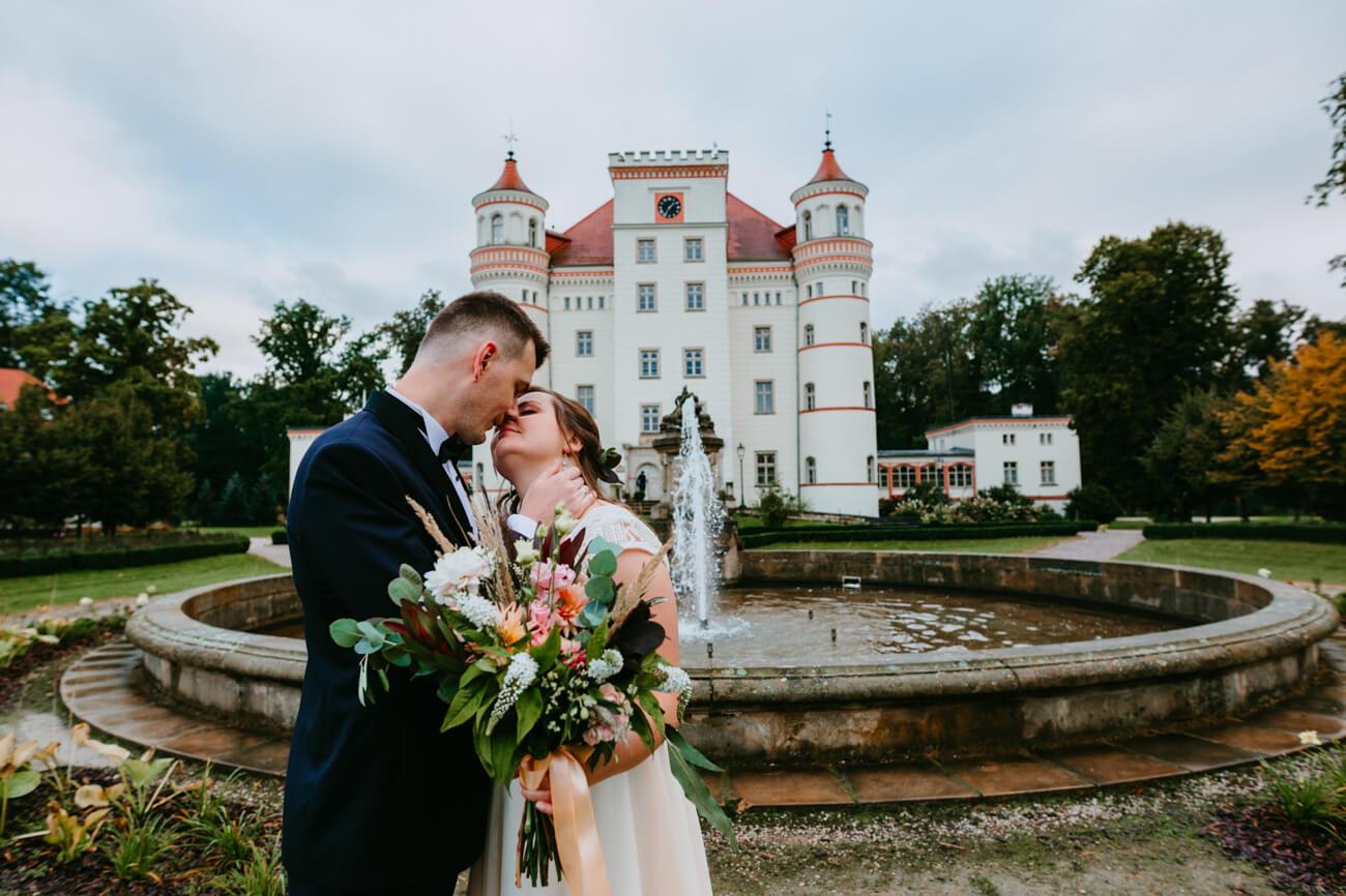 całująca się para młoda na tle zamku